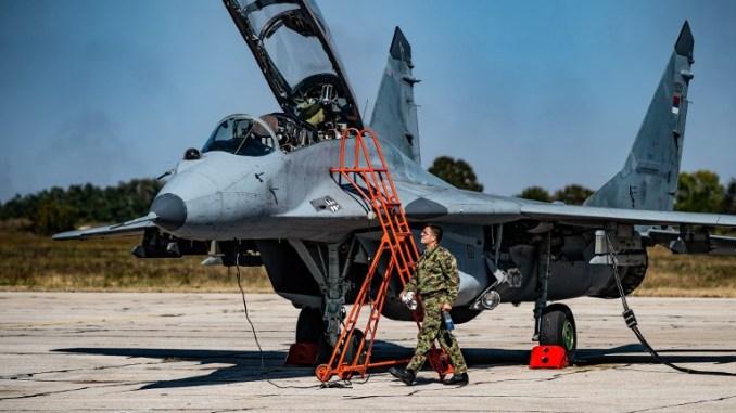 """ضابط يستعدّ لتشغيل طائرة مقاتلة من طراز """"ميغ-29"""" تابعة لسلاح الجو الصربي في مطار باتاجنيكا العسكري بالقرب من العاصمة بلغراد، في 4 تشرين الأول/أكتوبر 2018 (AFP)"""