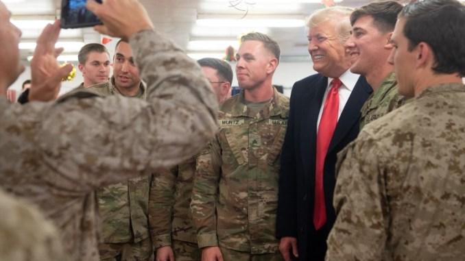الرئيس الأميركي دونالد ترامب يحيي أعضاء من الجيش خلال رحلة لم يعلن عنها مسبقًا إلى قاعدة الأسد الجوية في العراق في 26 كانون الأول/ديسمبر 2018 (AFP)