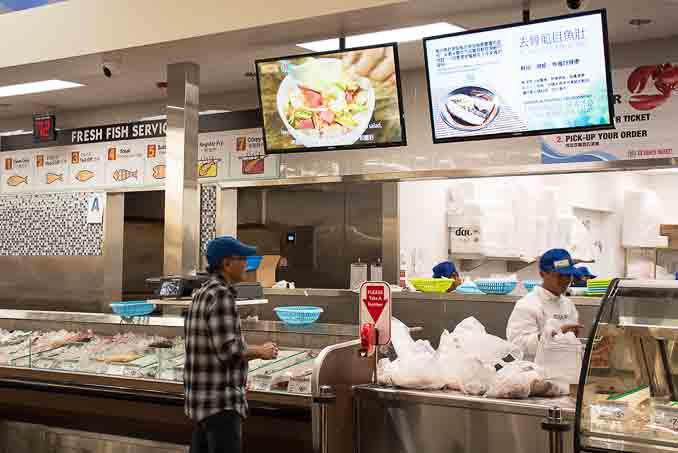 99大华超市在圣地亚哥南郡Chula Vista的新店4月1日正式开张,成为大圣地亚哥地区的第三家99大华超市。图为该超市的鱼类区,提供免费处理以及蒸、炸鱼服务,还有电视屏幕显示中国菜做法演示。(摄影:杨婕)