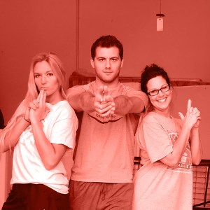 Red gradient map image of employees doing charlie's angel pose.