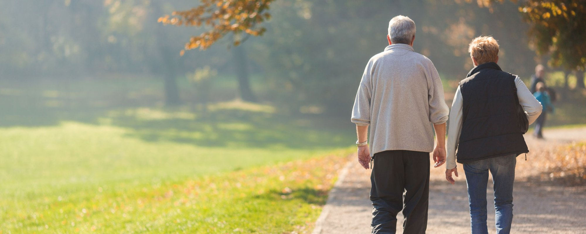 older adult couple walking through the park
