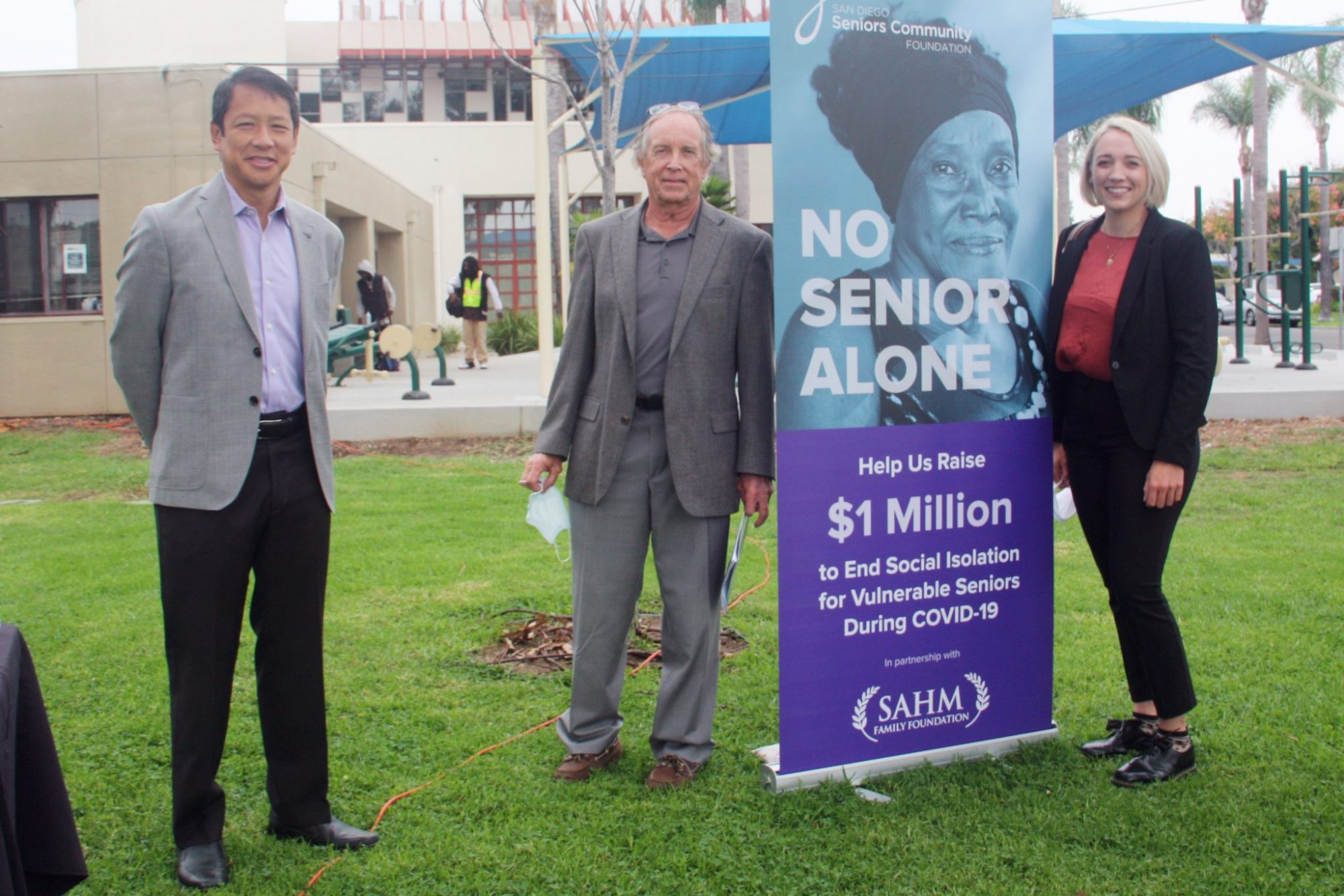 Ted Chan, Bob Kelly, and Abigail Sahm stand next to a banner for the $1 Million No Senior Alone campaign