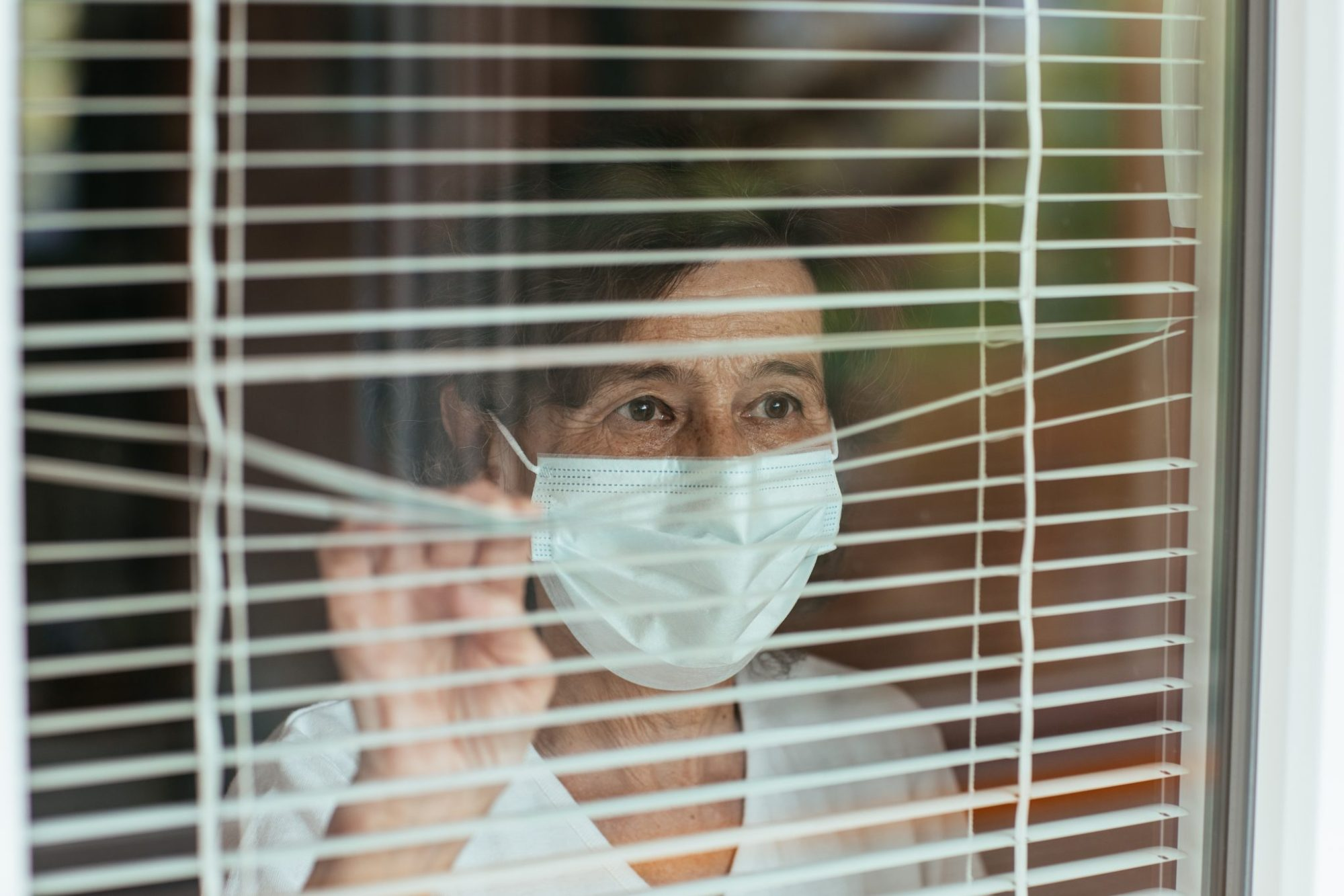 an older woman wearing a face mask, standing at a window and peering out through the blinds