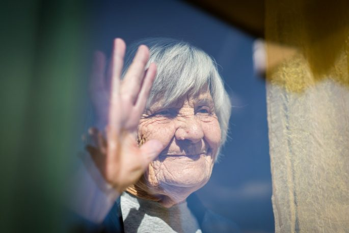 An older woman standing at a window looking out and waving