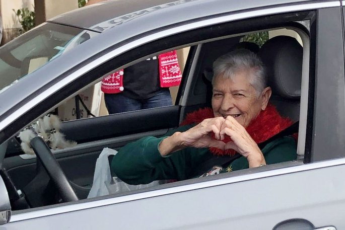 an older woman in her car makes a heart symbol with her hands at a drive-thru event at the Fallbrook senior center in North County