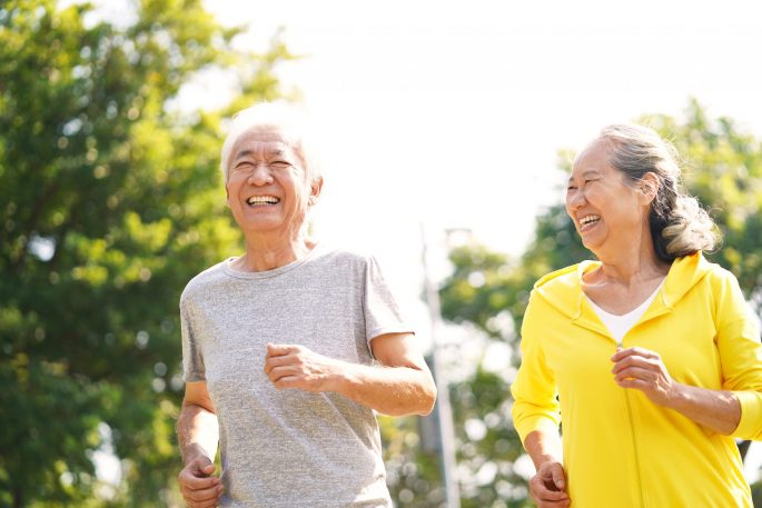 An older, smiling, husband and wife couple jogging outdoors