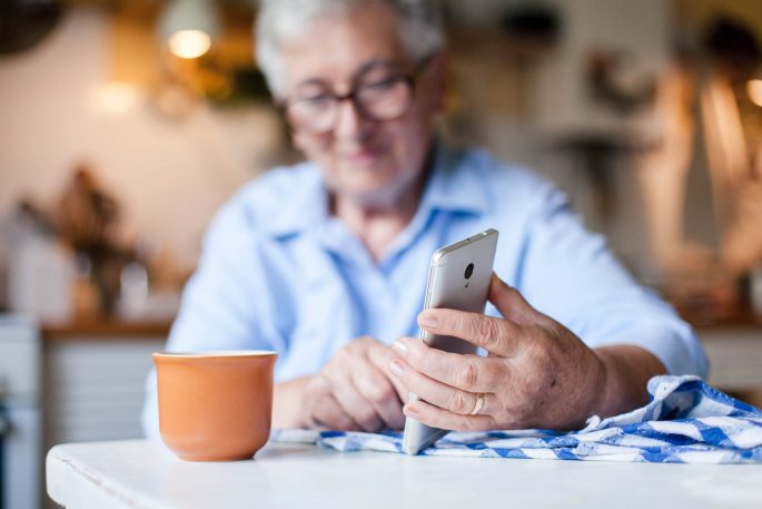 An older woman sits at her kitchen table with a cup of tea and her phone