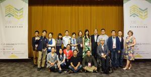 這張照片有19位來自各國的與會者,兩側為一層樓高的論壇海報