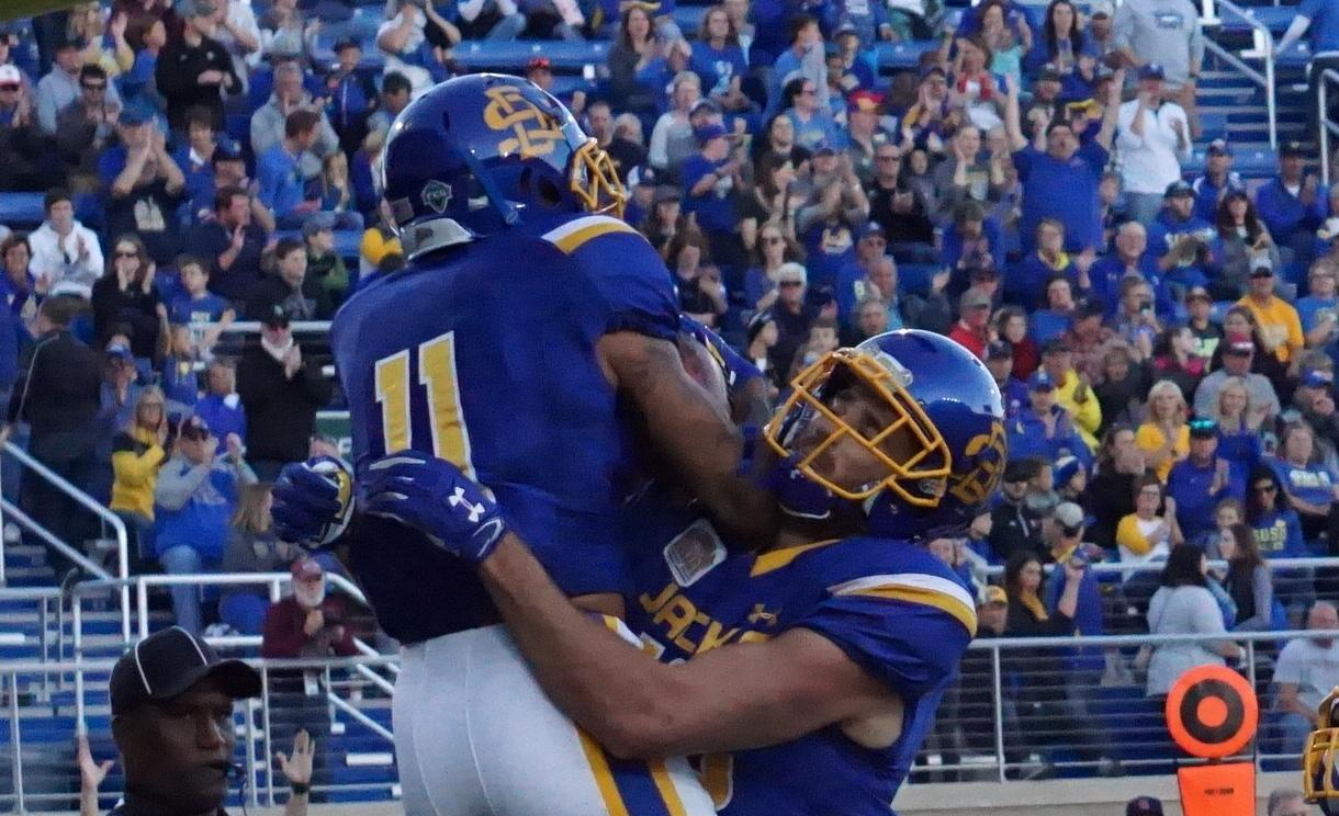 MEREDITH SUESS The team celebrates the touchdown made by Lewis during the first half of the game against Salukis Oct. 7.