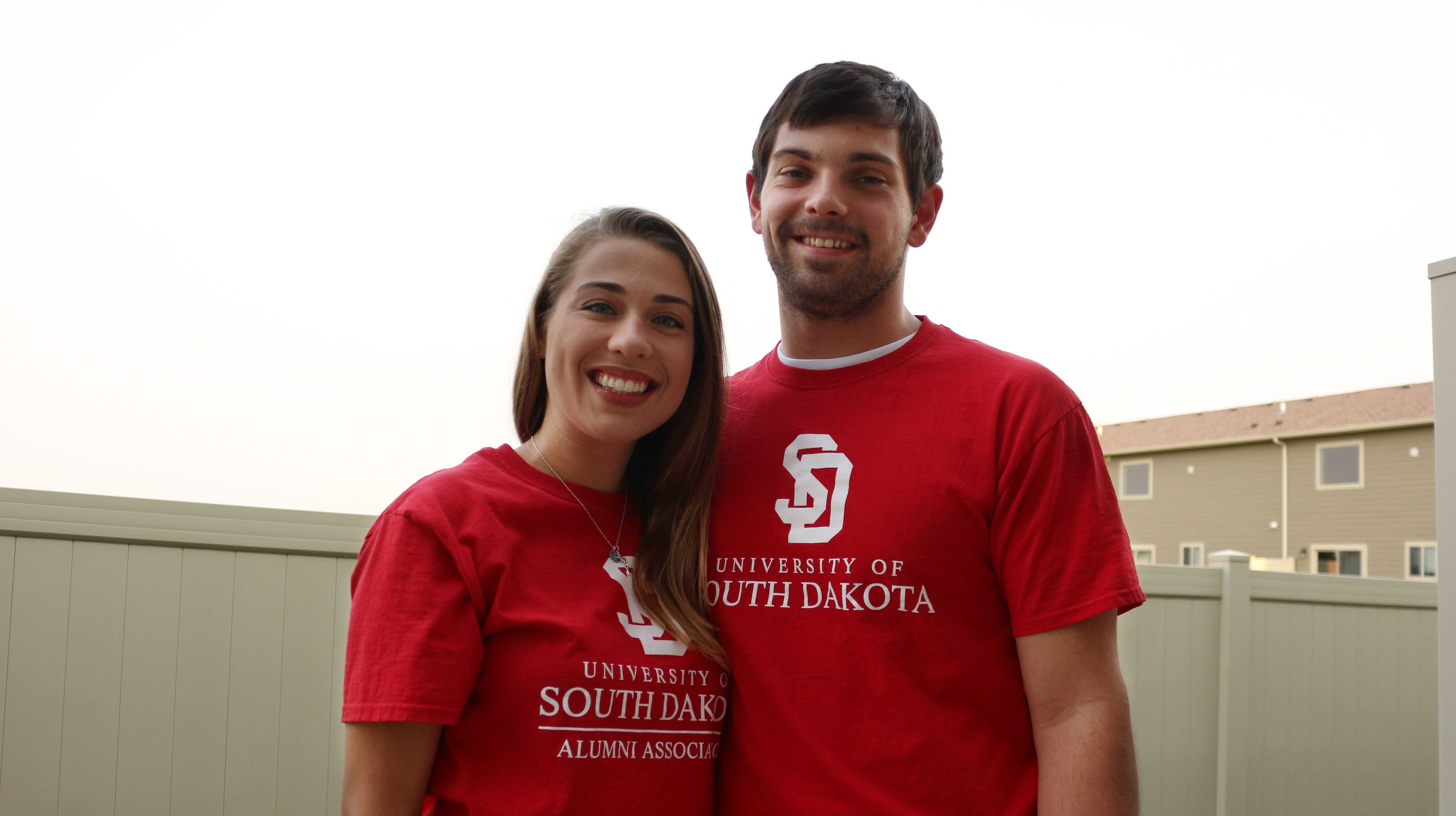 """IAN LACK Arianne Aasen and Casson Dennison wear T-shirts the University of South Dakota Alumni Association sent them to commemorate their engagement and acknowledge the SDSU-USD rivalry. On the back, Dennison's reads, """"I love a Coyote,"""" while Aasen's reads, """"Once a Coyote, Always a Coyote."""""""