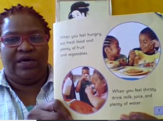 teacher showing page from healthy book