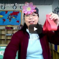 teacher shows paper flower pedals
