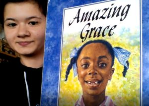 teacher showing the book amazing grace
