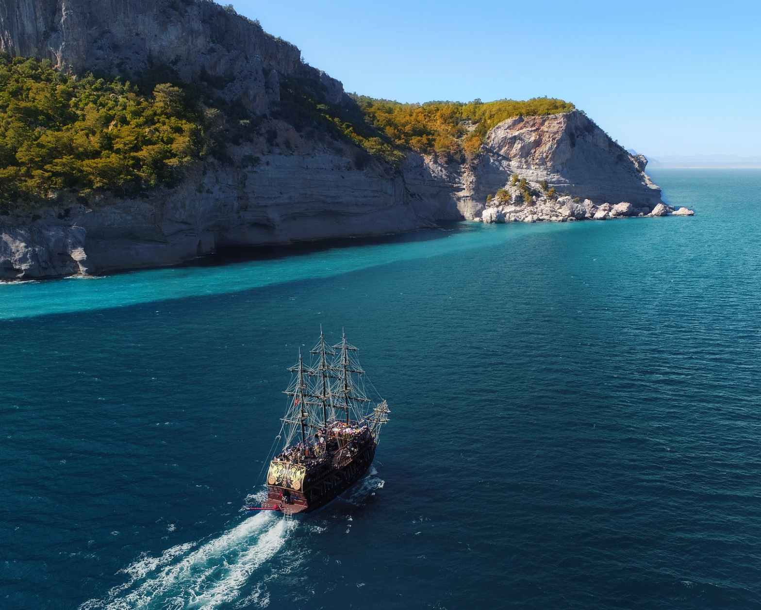 old ship floating in sea near mountainous island with plants