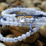 Three 4Ocean bracelets sit on stoney beach each made from recycled fishing nets and ocean plastic.