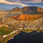A view of Cape Town from above. The sea is in the foreground with Table Mountain in the background.