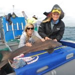 Two volunteers are holding a shark on a catch-and-release shark research trip in South Africa.