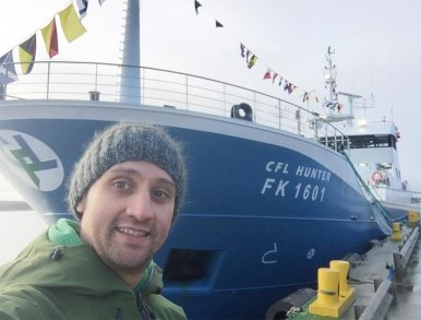 Selfie with large docked ship in background