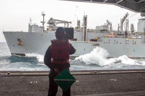170509-N-PF593-133 WATERS SOUTH OF JAPAN (May 9, 2017) Seaman Christian Berhane-Haile, from Montgomery, Alabama, signals to Sailors aboard Military Sealift Command dry cargo and ammunition ship, USNS Charles Drew (T-AKE 10), from the hangar bay of the Navy's forward-deployed aircraft carrier, USS Ronald Reagan (CVN 76), during a replenishment-at-sea. As the signaler, Berhane-Haile signaled to haul in or feed out line during the transfer of ordnance from Charles Drew to Ronald Reagan. Ronald Reagan, the flagship of Carrier Strike Group 5, provides a combat-ready force that protects and defends the collective maritime interests of its allies and partners in the Indo-Asia-Pacific region. (U.S. Navy photo by Mass Communication Specialist 2nd Class Jamal McNeill/Released)