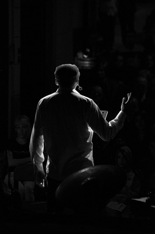 Man singing in theater, viewed from behind.