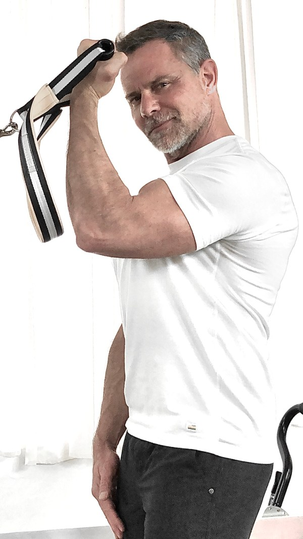 Sean posing with pilates equipment