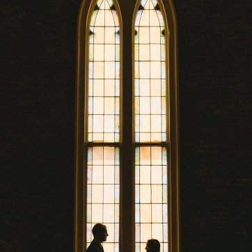 Bride and groom silhouetted in front of church stained glass windows
