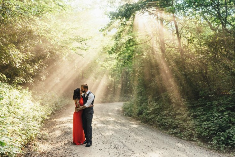 woman in red dress and her fiancé stand among the forest trees looking at each other during their asheville engagement photos