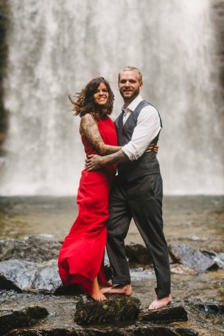 woman in red dress with fiancé kiss each other among the forest of Asheville during their engagement session