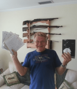 """Ken Kinsler posing with his writing and a copy of his book, """"Think Snow"""""""