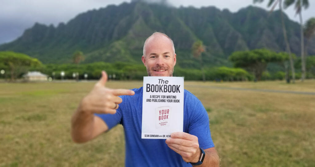 """Sean, posing with a copy of his writing manual, """"The BookBook""""."""