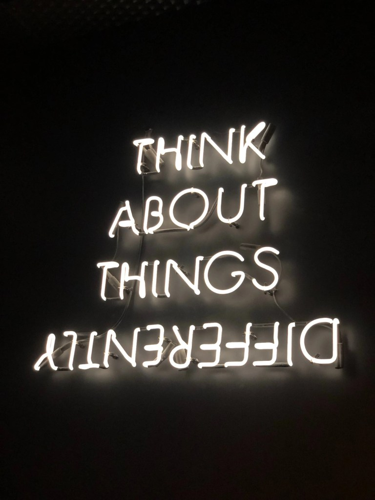 "A neon sign saying ""Think about things differently"""