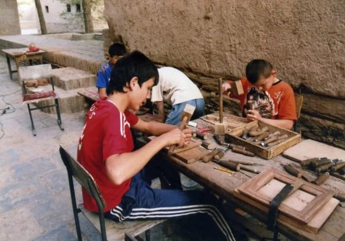 木彫り細工を行う少年達