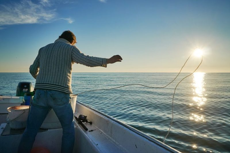 man tossing fishing line from boat