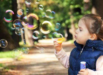 blowing bubbles, little girl