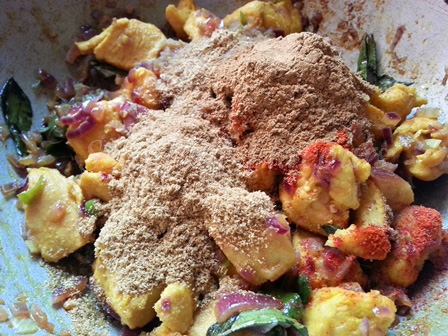 Add spice powders to the chicken for kodi recipe