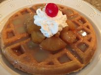 Waffle topped with pineapple, whipped cream and salted caramel sauce