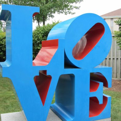 Metal sculpture bright blue spelling love.