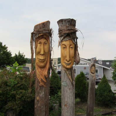 Close up of two wooden scuptures, men's faces.