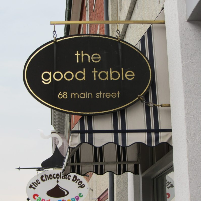Black and gold oval table shaped sign for the Good Table.