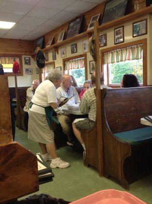 A waitress at Moody's Diner taking a order.