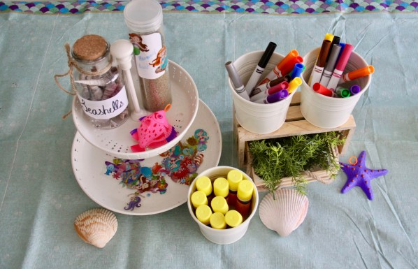mermaid birthday party craft supplies on a table