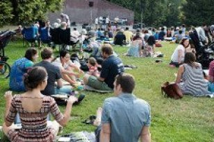 color photo of several people sitting on a lawn or in lawn chairs, facing toward a brick and concrete outdoor stage seen iin the distance.
