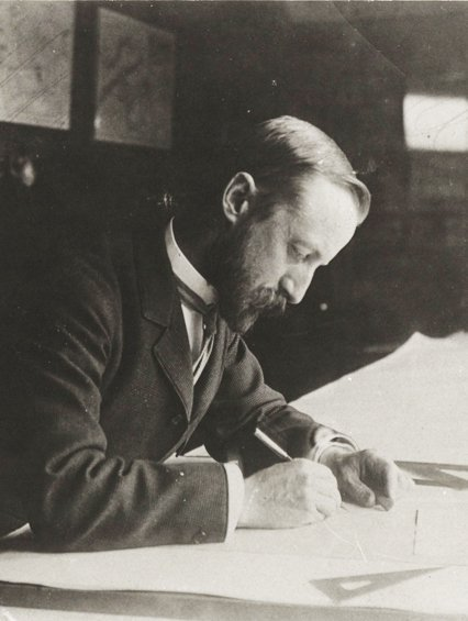 black and white image of John Charles Olmsted working on a drawing at his desk