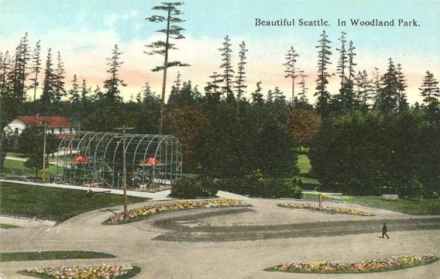 "Colorized photo with caption, ""Beautiful Seattle. In Woodland Park."" Image is slightly aerial view of unpaved turnaround bordered by flowering groundcover, with conifer trees and a glimpse of lawn in the background."