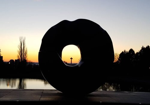 photo taken at sunset with sculpture, landform and trees in dark profile against western sky.
