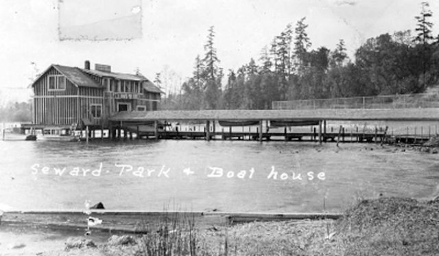 black and white photo of wooden building on pier and connected by long covered boardwalk