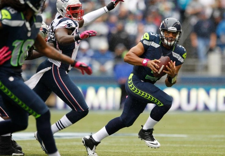 Seattle Seahawks' Russell Wilson being chased by New England Patriot