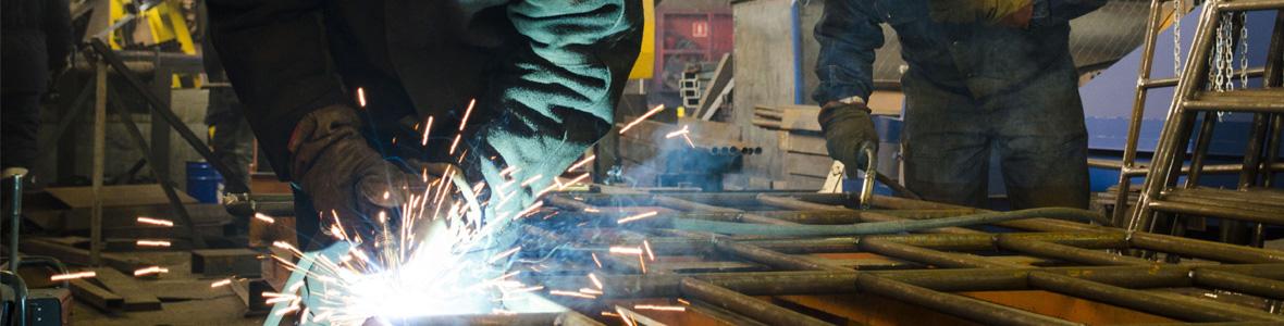 Two welders working on large metal frame
