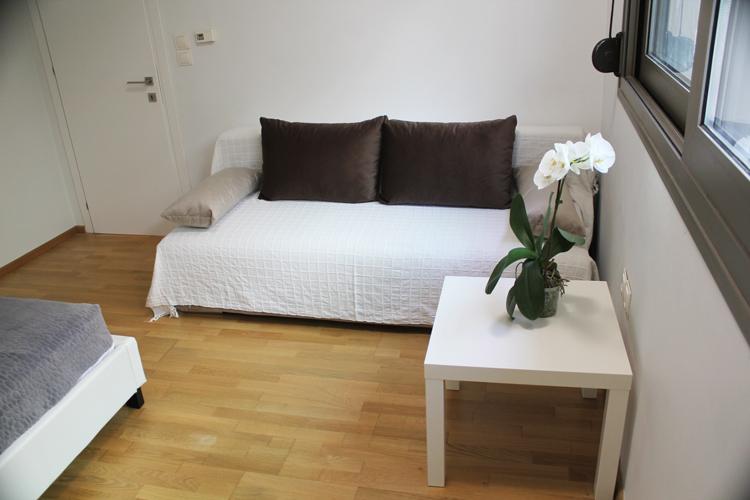 Спальня с видом на скалу, с очень большой двуспальной кроватью и диваном-кровать