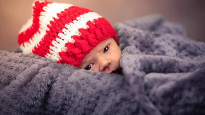 bébé avec un bonnet emmitouflé dans une couverture - baby-blanket